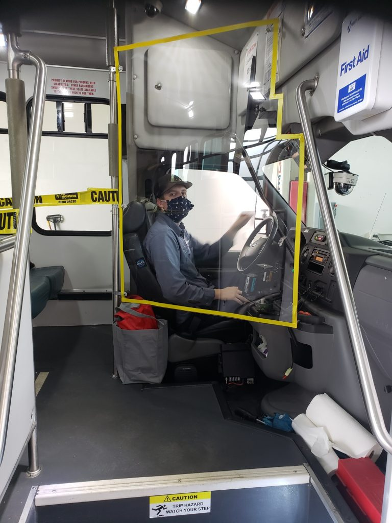 Bus Driver behind plastic shield wearing face mask